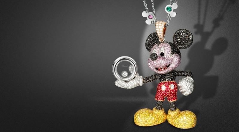 Кулон с Микки Маусом из коллекции Happy Mickey: белое, розовое и желтое золото с черными, желтыми, розовыми и бесцветными бриллиантами, рубинами и ониксом. Цепочка из белого золота, украшена голубыми и розовыми сапфирами, изумрудами, рубинами и аметистами.