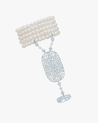 Жемчужный браслет, соединяющийся с кольцом крупным элементом из платины с бриллиантами, изображающими цветочный узор