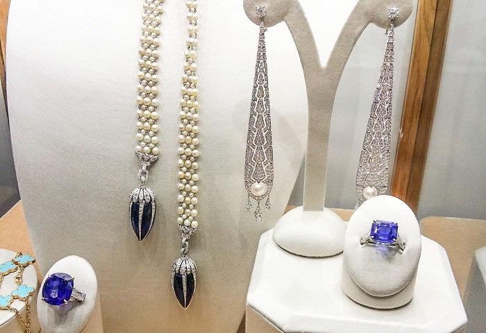 Слева направо: кольцо с бирманским сапфиром весом 29,65 карата и бесцветными бриллиантами по бокам; жемчужное колье «Лассо» с подвесками из синего стекла, украшенными бриллиантами, приблизительно 1900 год; серьги Cartier с жемчугом и бриллиантами; платиновое кольцо с кашмирским сапфиром 9,43 карата и бесцветными бриллиантами