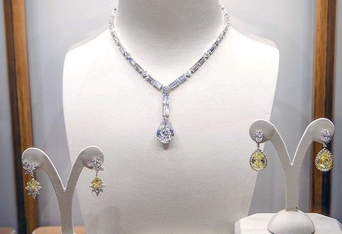 По центру — колье с бесцветными бриллиантами, в том числе центральным грушевидным камнем весом 27,03 карата; слева — серьги с двумя желтыми ромбовидными бриллиантами общим весом 8,03 карата и 24 бесцветными бриллиантами; справа — серьги с двумя грушевидными желтыми бриллиантами весом 13,76 и 14,18 карата, двумя овальными бесцветными бриллиантами и паве из мелких бесцветных бриллиантов
