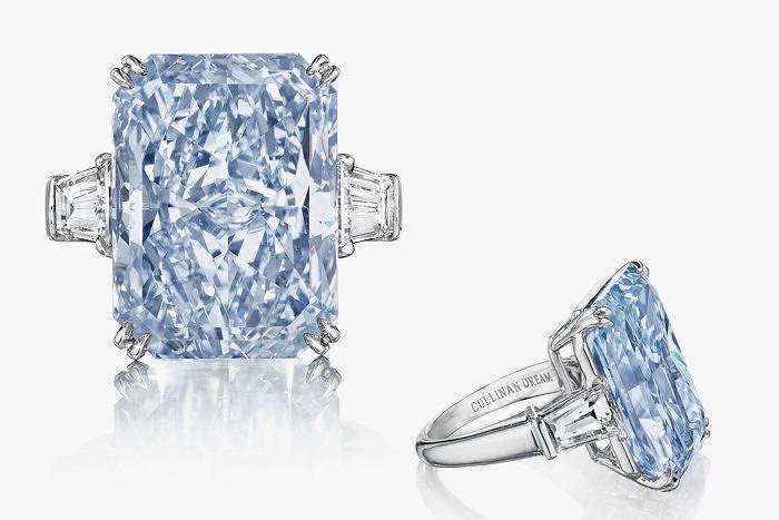 Бриллиант Cullinan Dream инкрустирован в платиновое кольцо, дополнительно украшенное двумя бесцветными бриллиантами огранки багет.