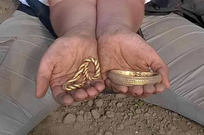 Мэри Аагаард Держит в руках два найденных золотых браслета