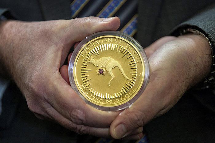 Представитель The Perth Mint держит в руках монету Kimberley Treasure